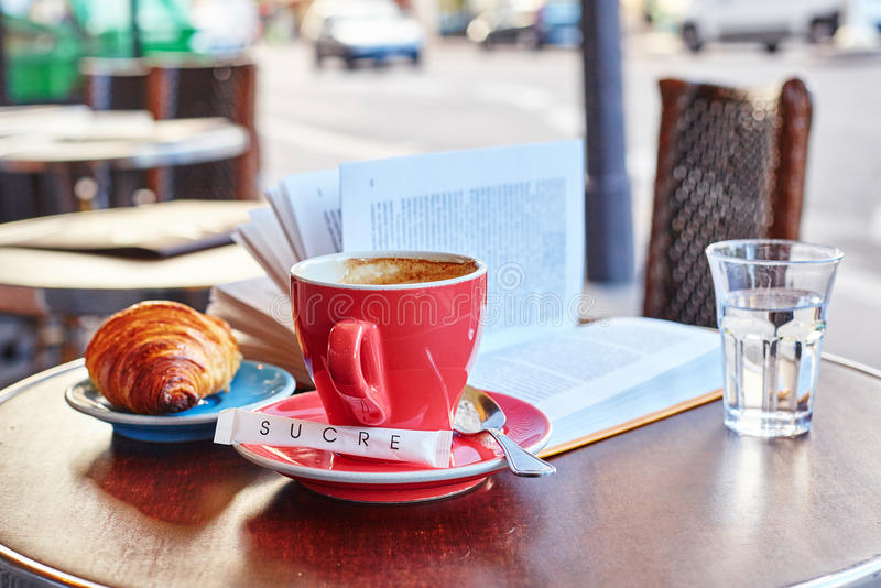 Breakfast in a Parisian street cafe. Cup of coffee, croissant and book royalty free stock photography
