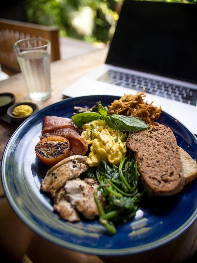 A breakfast plate with omelette, brown bread, bacon and vegetables near a laptop on a table royalty free stock photos