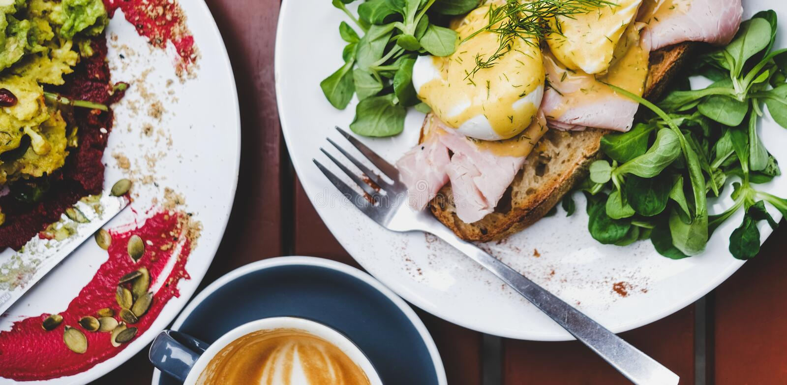 Breakfast with poached eggs on bread and coffee, wide composition. Trendy breakfast set. Flat-lay of poached Eggs Benedict on sourdough bread toast with green stock image
