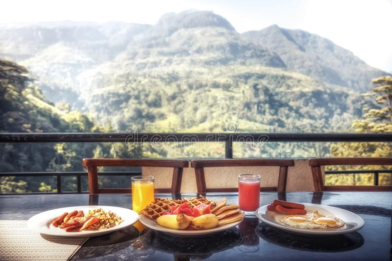 Breakfast in restaurant with beautiful view on mountains range in summer sunny morning during travel holidays royalty free stock photography