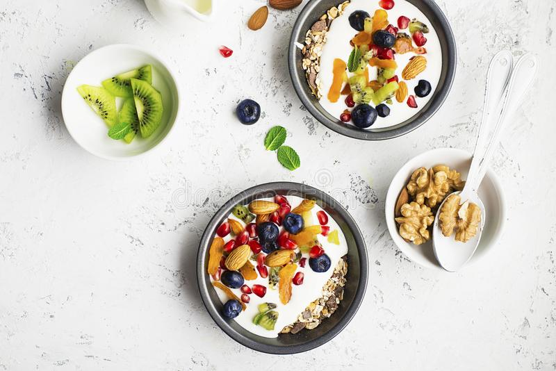 Breakfast, rice porridge or natural yoghurt with assorted berries, fruits and nuts: kiwi, pomegranate, blueberries royalty free stock photos