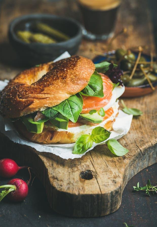 Breakfast with salmon, avocado, cream-cheese, basil bagel, espresso coffee stock image