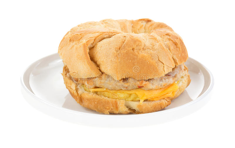 Breakfast Sandwich On Dish Side. A top view of a nicely browned prepared breakfast croissant filled with a sausage patty, egg, cheese on white stock images