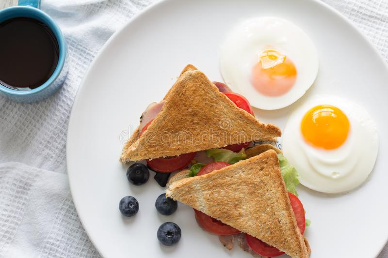 Breakfast. Sandwich with ham and tomatoes on plate stock photography