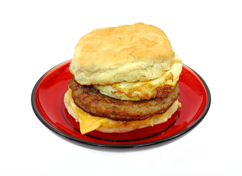 Breakfast Sandwich On Red Plate. A freshly made sausage egg and cheese breakfast sandwich on a red plate stock photos