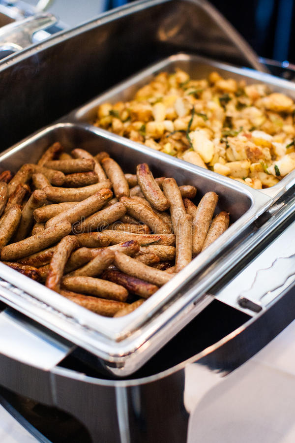 Breakfast sausage at a buffet. Breakfast sausages and potatoes at a buffet at a hotel stock photo