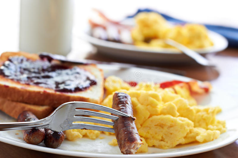 Breakfast with sausage links and scrambled eggs. Sausage links being pick up by a fork at a big breakfast royalty free stock images