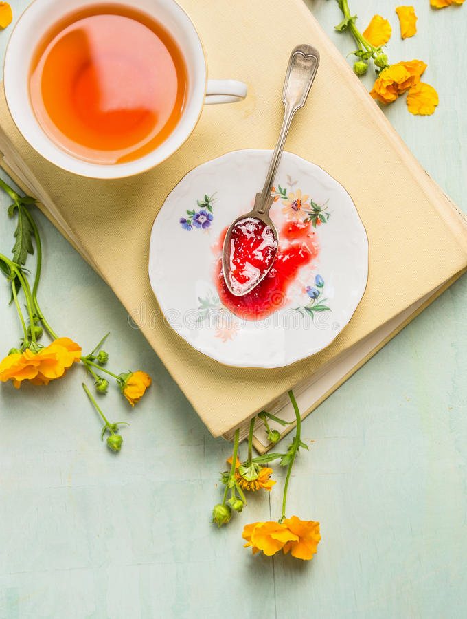 Breakfast scene: cup of tea, plate with red jam and vintage spoon on a book and yellow garden flowers. Still life, top view stock image