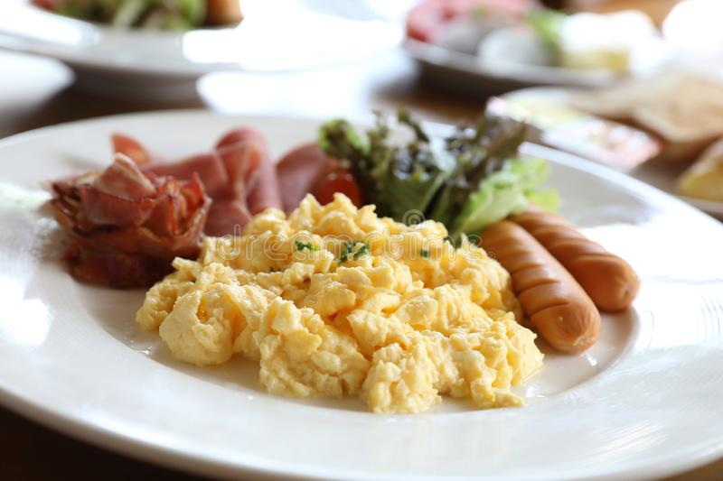 Breakfast scrambled egg with bacon sausage and salad on wood backgroun royalty free stock photo