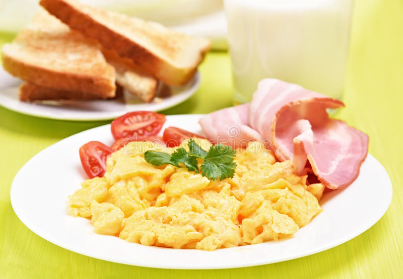 Breakfast scrambled eggs with bacon and tomatoes royalty free stock photos