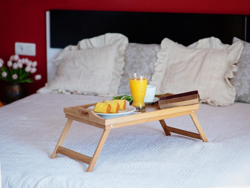 Breakfast served in bed on a wooden tray with tea, juice, cookies. Hotel room service, relax concept stock images