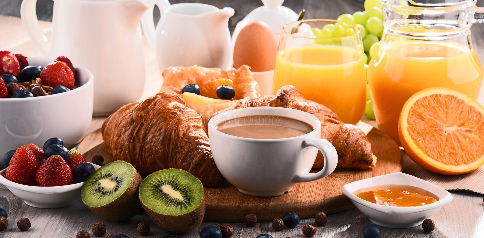 Breakfast served with coffee, juice, croissants and fruits royalty free stock photo