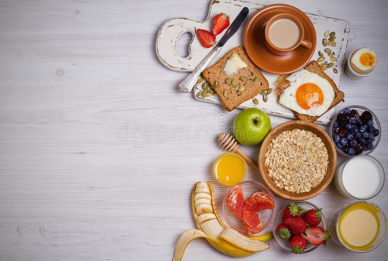 Breakfast served with coffee, orange juice, cereals, milk, fruits, eggs and toasts. Balanced diet, food banner, background royalty free stock images