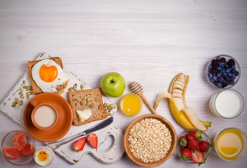 Breakfast served with coffee, orange juice, oat cereal, milk, fruits, eggs and toast. Balanced diet. Morning sweet and savory meal, food background. overhead stock image