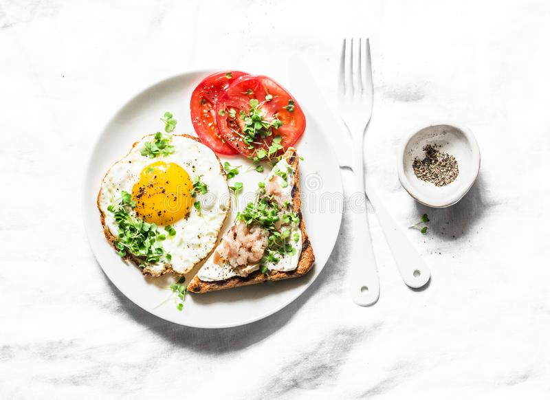 Breakfast served - fried egg, smoked mackerel cream cheese toast, tomatoes on a light background royalty free stock photo