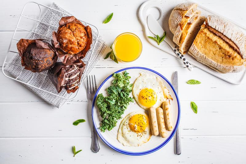 Breakfast served with fried eggs, salad, muffins and orange juice on white wooden table. royalty free stock images