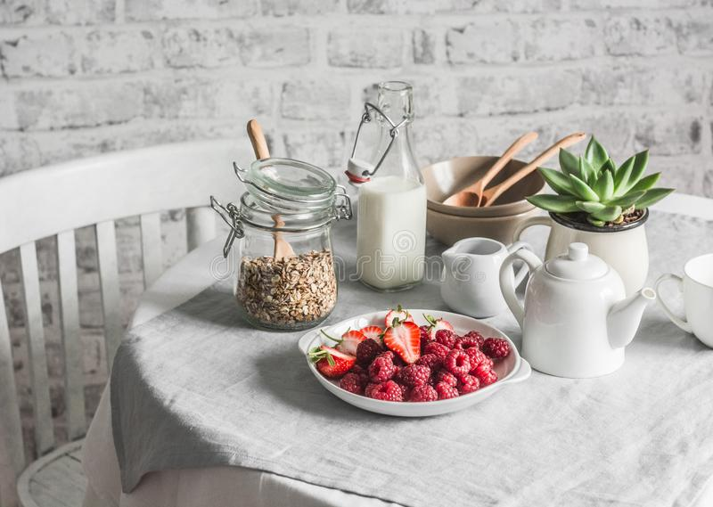 Breakfast served table - granola, milk, fresh raspberries and strawberries in the bright kitchen. Flat lay.  stock image