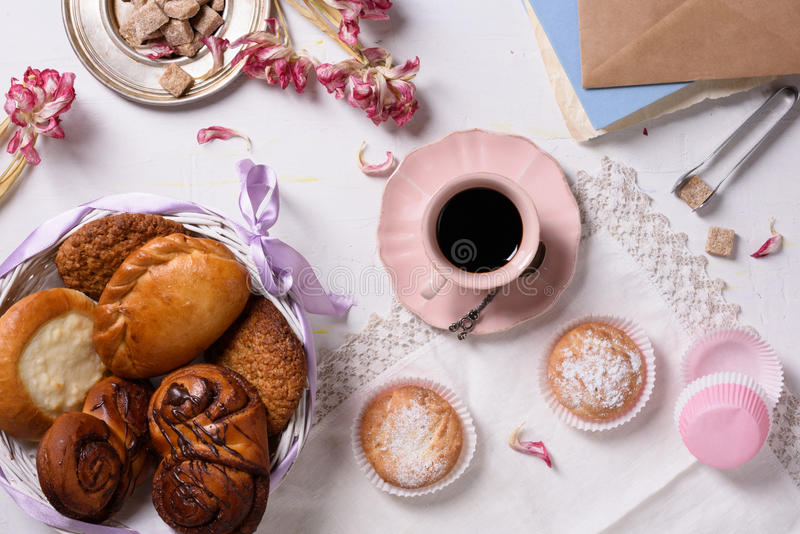 A breakfast served with a variety of pastries, desserts, coffee, sugar and tulip petals. Copy space, top view. A breakfast served with a variety of pastries stock photography