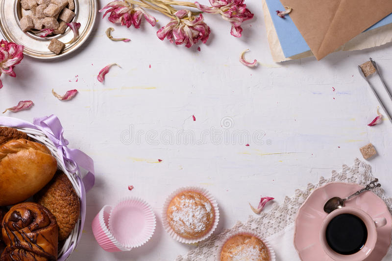 A breakfast served with a variety of pastries, desserts, coffee, sugar and tulip petals. Copy space, top view. A breakfast served with a variety of pastries royalty free stock photo