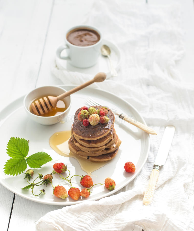 Breakfast set. Buckwheat pancakes with fresh garden strawberries, honey and cup of coffee over white wooden background stock image