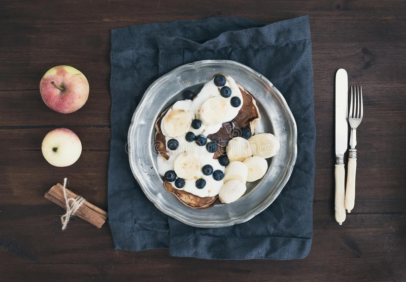 Breakfast set on dark wooden desk: apple and cinnamon pancakes royalty free stock photos
