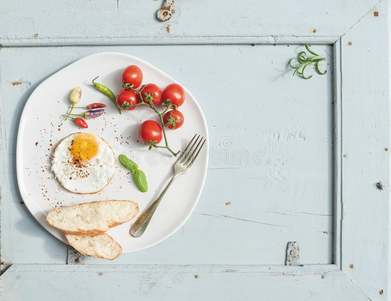 Breakfast set. Fried egg, bread slices, cherry tomatoes, hot peppers and herbs on white ceramic plate over light blue. Wooden backdrop, top view, copy space stock photo