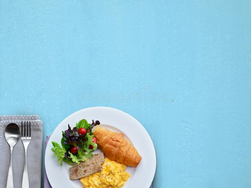 Breakfast set on left corner and blue background. Copy space stock photography