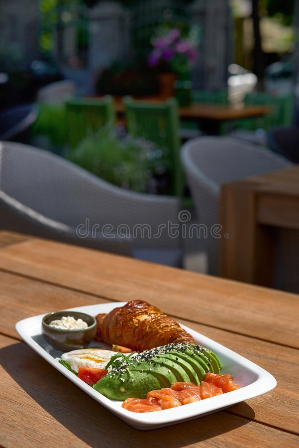 Breakfast is set. Whole grain sandwich with fried egg, red fish, avocado and greens on a rustic wooden table, morning. Mood, top view, horizontal royalty free stock image