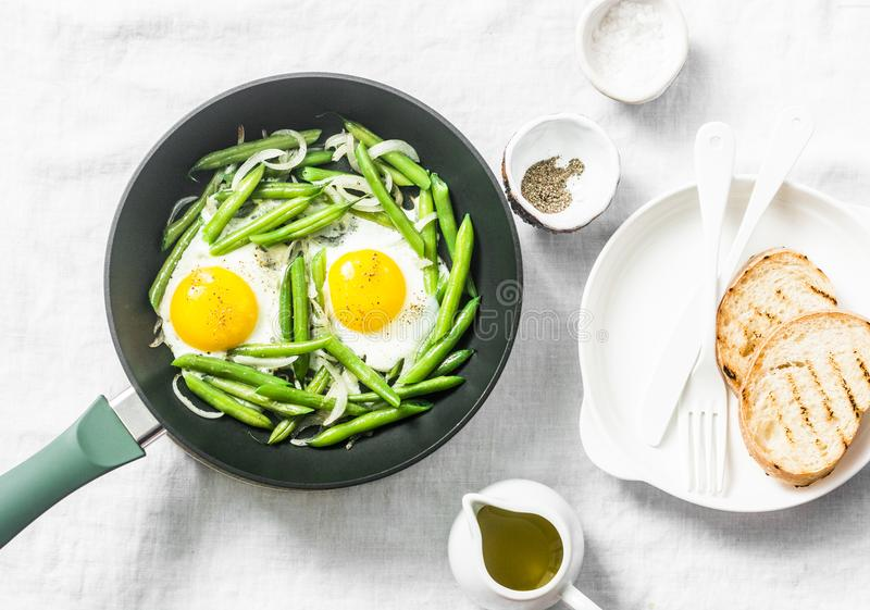 Breakfast skillet. Fried eggs with green beans. Healthy eating concept on white background, top view. Flat lay royalty free stock photo