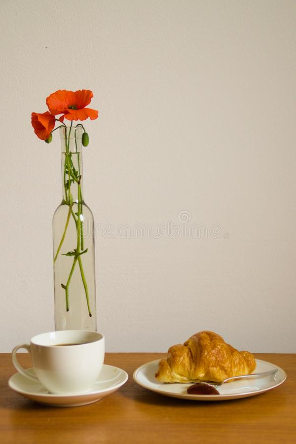 Breakfast Still Life With Poppies. Still life with table set up for breakfast with cup of strong black coffee, croasaint and vase with two poppies with copy stock photography