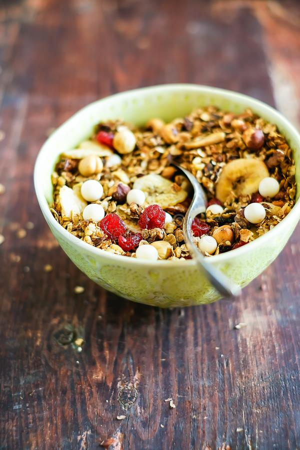 Breakfast super bowl with granola or muesli with oat flakes, banana chips, dried cherry, hazelnuts and white chocolate on a wooden royalty free stock photos