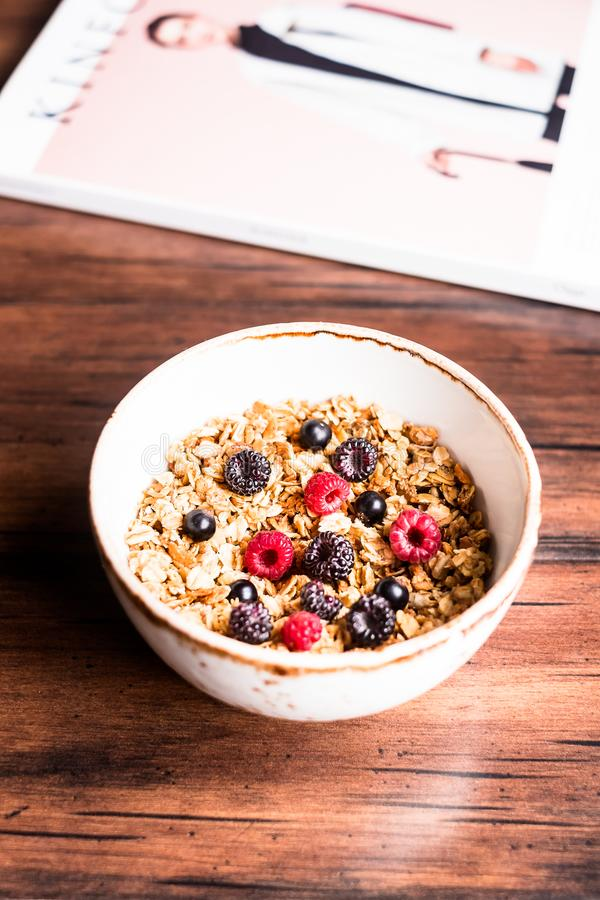 Breakfast super bowl of homemade granola or muesli with oat flakes, black currant, black raspberry and peanuts on a wooden table, royalty free stock photography