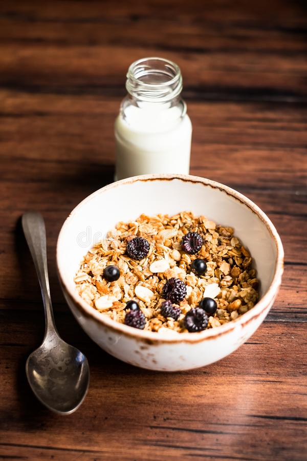 Breakfast super bowl of homemade granola or muesli with oat flakes, black currant, black raspberry and peanuts on a wooden table, royalty free stock photos