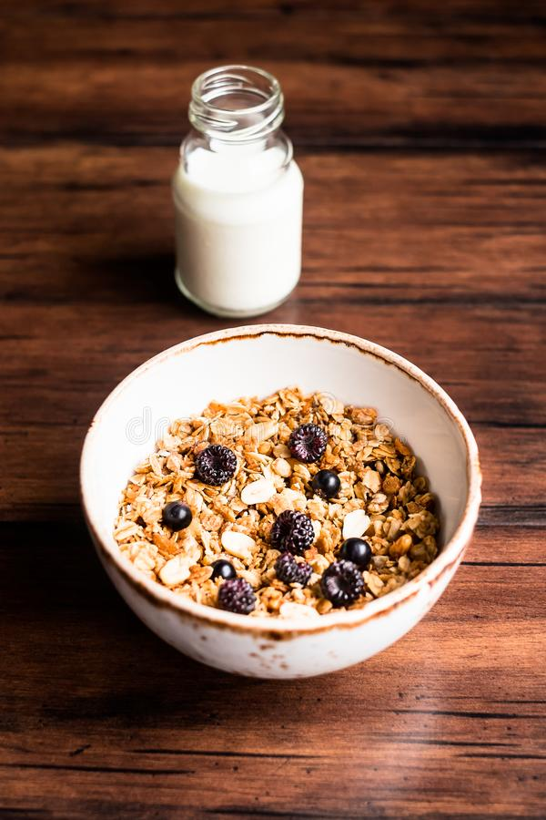 Breakfast super bowl of homemade granola or muesli with oat flakes, black currant, black raspberry and peanuts on a wooden table, stock image