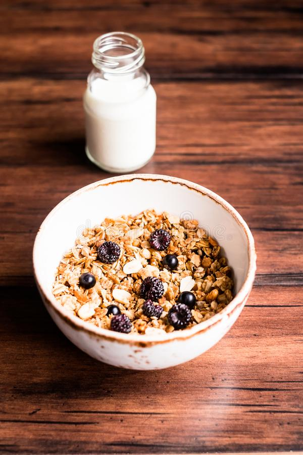 Breakfast super bowl of homemade granola or muesli with oat flakes, black currant, black raspberry and peanuts on a wooden table, stock photo