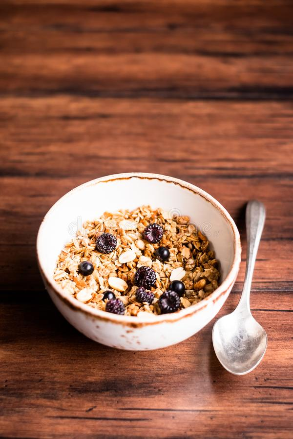 Breakfast super bowl of homemade granola or muesli with oat flakes, black currant, black raspberry and peanuts on a wooden table, royalty free stock images