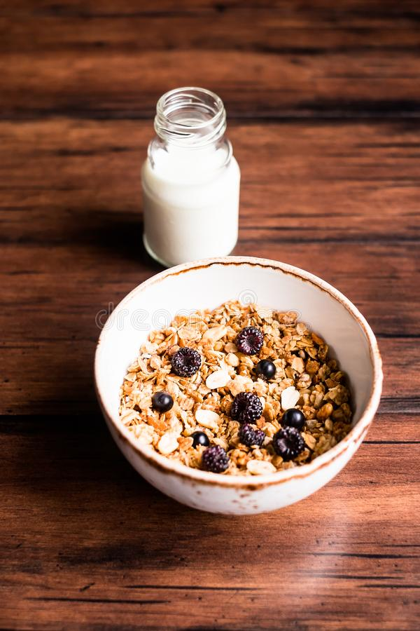 Breakfast super bowl of homemade granola or muesli with oat flakes, black currant, black raspberry and peanuts on a wooden table, stock photos