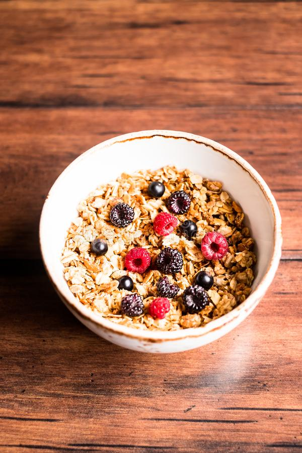Breakfast super bowl of homemade granola or muesli with oat flakes, black currant, black raspberry and peanuts on a wooden table, stock photography