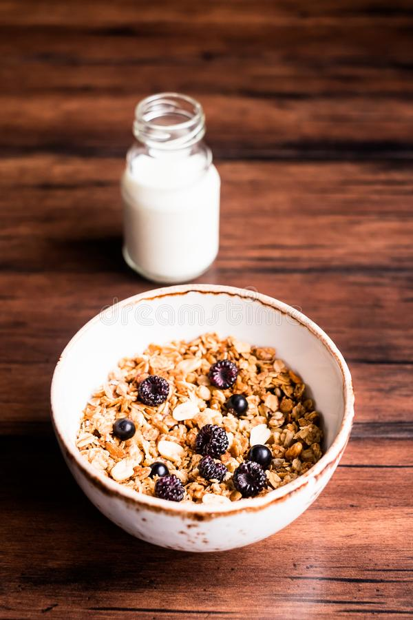Breakfast super bowl of homemade granola or muesli with oat flakes, black currant, black raspberry and peanuts on a wooden table, royalty free stock photo