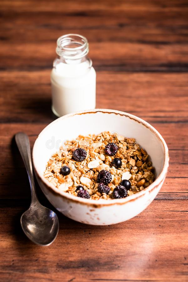 Breakfast super bowl of homemade granola or muesli with oat flakes, black currant, black raspberry and peanuts on a wooden table, stock images