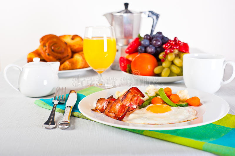 Breakfast table. Table set up for breakfast: fruits, pastry, fried egg with vegatables and bacon royalty free stock photo