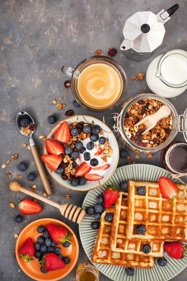 Breakfast table with cereal granola, milk, fresh berries, coffee. Healthy breakfast table with cereal granola, milk, fresh berries, coffee and waffles, top view royalty free stock photo