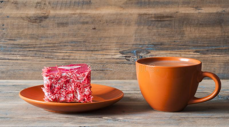 Cup of coffee and cake with heart on dark wooden table. Breakfast table consisting of red cupcake with heart and a cup of coffee royalty free stock image