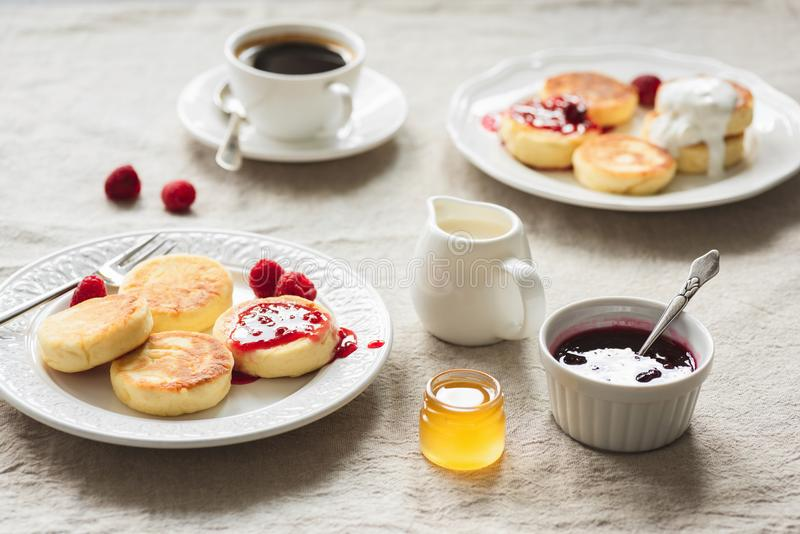 Breakfast Table With Curd Fritters or Pancakes, Coffee, Jam and Honey stock image