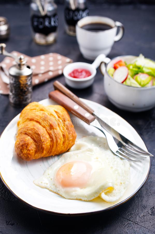 Breakfast. On a table, fried eggs and croissant royalty free stock image