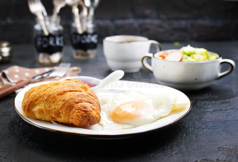 Breakfast. On a table, fried eggs and croissant stock images