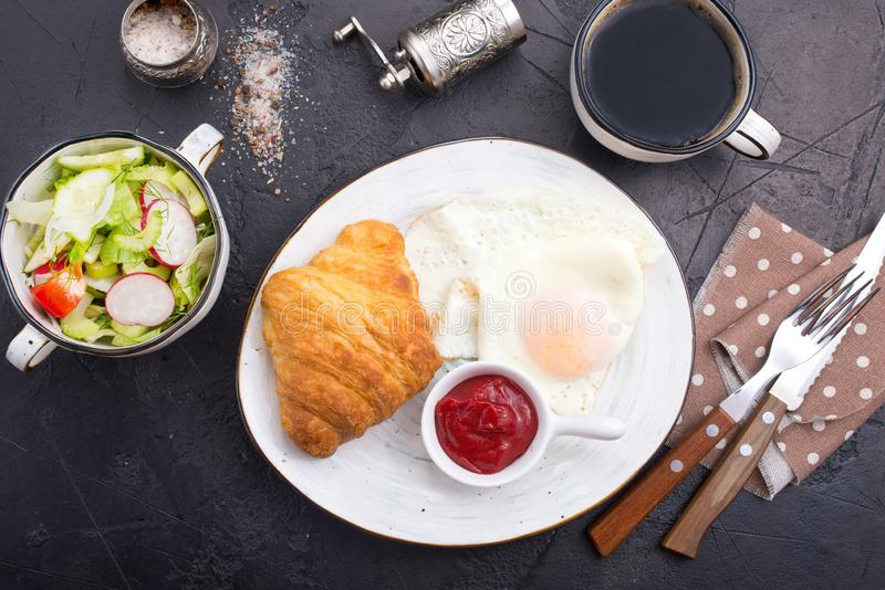 Breakfast. On a table, fried eggs and croissant royalty free stock photography
