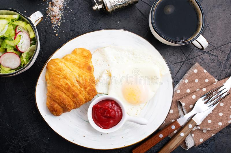 Breakfast. On a table, fried eggs and croissant stock image