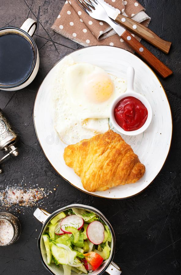 Breakfast. On a table, fried eggs and croissant royalty free stock photo