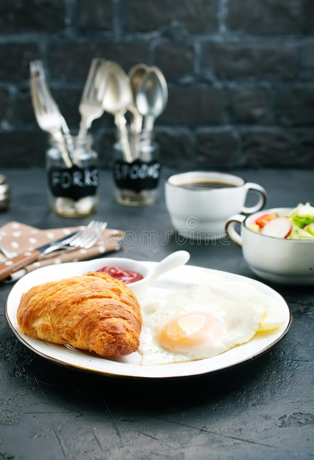 Breakfast. On a table, fried eggs and croissant royalty free stock images